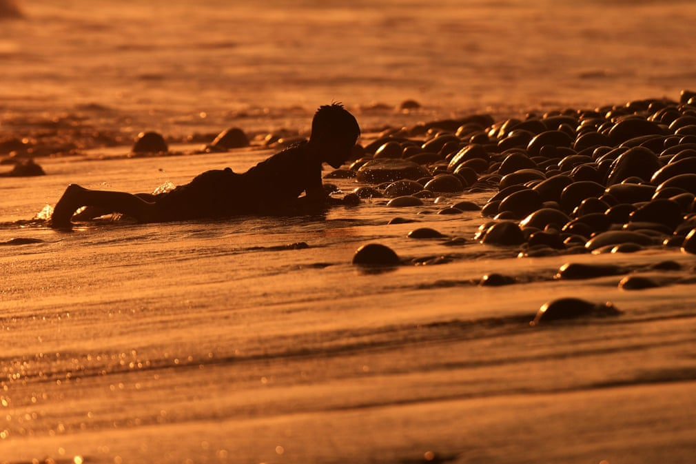 LaLibertad Peru A Boy Lies In The Sand As Sun Sets Over El Tunco Beach Photograph Marvin Recinos AFP Getty Images